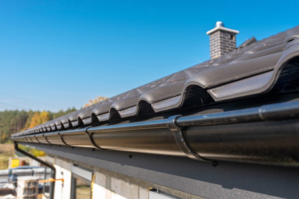 A metal, black gutter on a roof covered with ceramic tiles